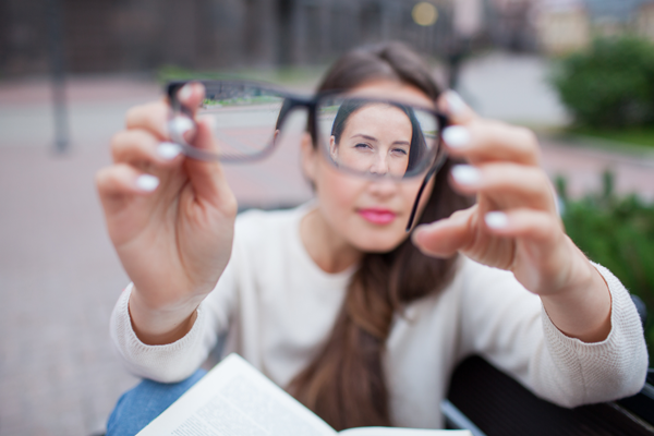 woman holding eye glasses